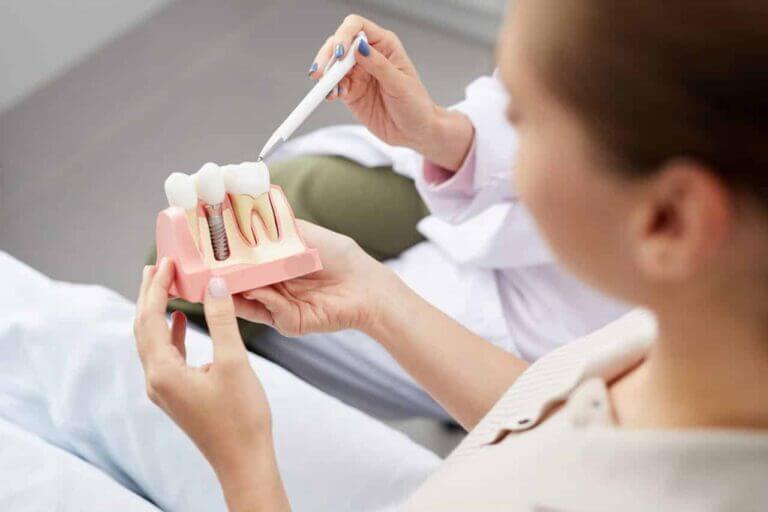 Zahnimplantate Wien - Frau beim Beratungsgespräch mit verschiedenen Implantaten